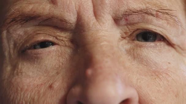 traurige alte Frau öffnet die Augen, Porträt aus nächster Nähe