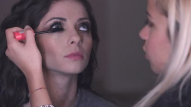 Makeup artist making up mascara on beautiful woman on set