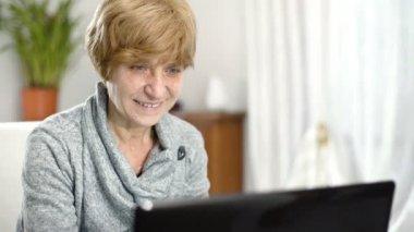Happy blond mature businesswoman working on computer