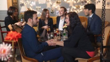 Young couple at the table with colleagues flirt and then toast with friends