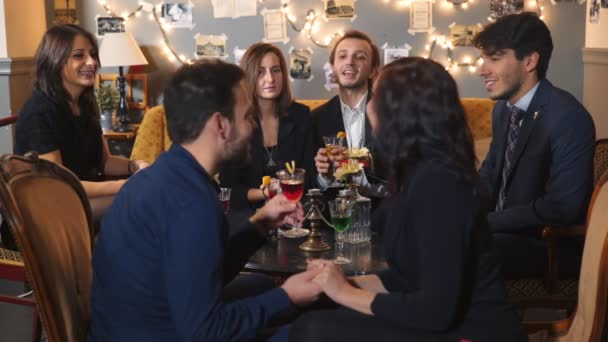 Group of elegant people at a table make a toast