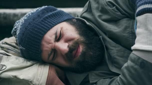 Obdachloser schläft, während der Fußgänger ihn weckt und Almosen hinterlässt