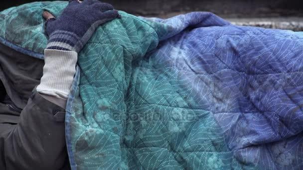 Obdachloser schläft, während unbekannte Hand ihn weckt und Almosen hinterlässt