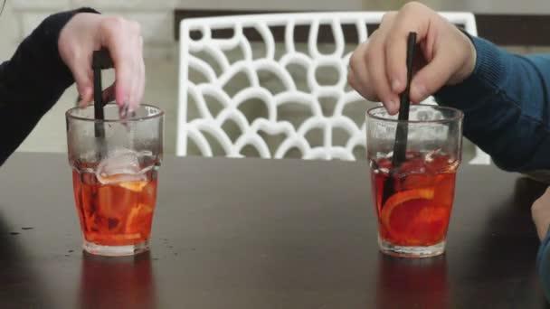 Zblízka pár rukou míchání koktejlů se slámou