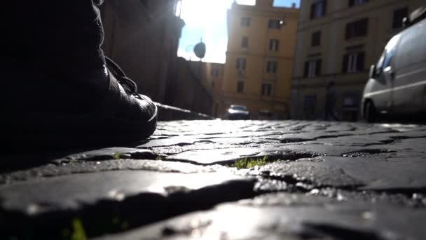 Detailní záběr na člověka boty chůzi na ulici ve městě po dešti