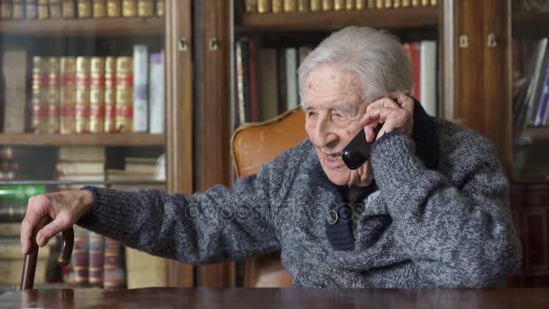 Starý děda mluví na telefon, opřen hůl
