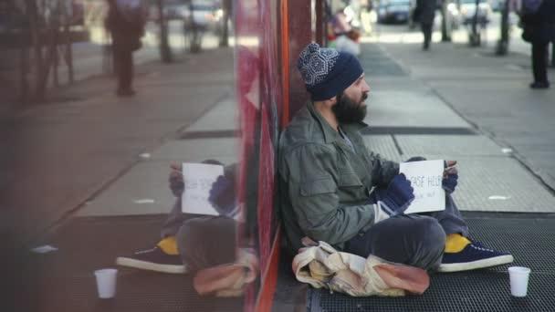 Traurige Obdachlose, die allein auf der Straße sitzen und Almosen erbetteln