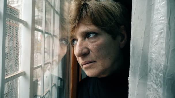 depresivní, přemýšlivý zralá žena v okně