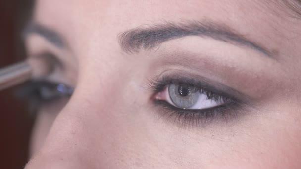 Detailní záběr na použití hnědé oční stíny na krásné ženské oči
