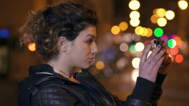 roztomilý sexy brunetka má selfie s smartphone v noci město, profil