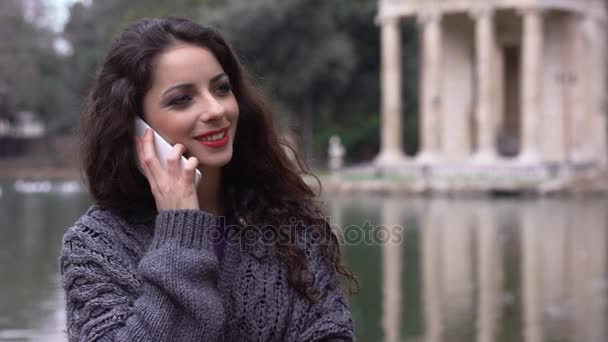 usmíval se, Bruneta mluvil telefonicky v parku, jezero v pozadí