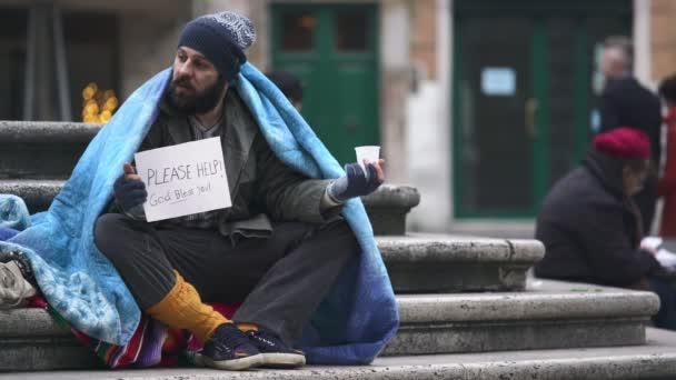 Obdachloser, der auf der Treppe sitzt, erhält Almosen von einem Mann