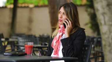 Smiling cute business woman sitting at cafe and talking by smartphone