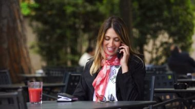Smiling cute Woman talking on Smartphone sitting in a bar- outdoor