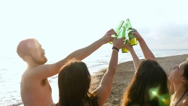 čtyři přátelé rádi na pláži opékání a pití spolu