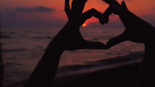Žena rukou ukazující srdce tvar rámování slunce v západu slunce