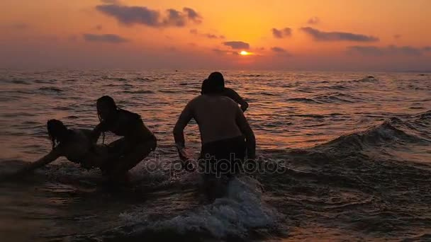 Water games at sea at sunset: joy, happiness, carefree
