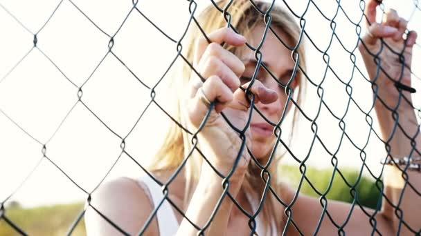 traurig deprimiert, blonden Frau Holding Maschendraht und beobachten ...