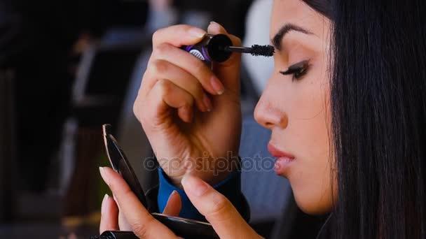 Mladých asijských hezká žena uvedení na řasenku a hledá zrcadlo