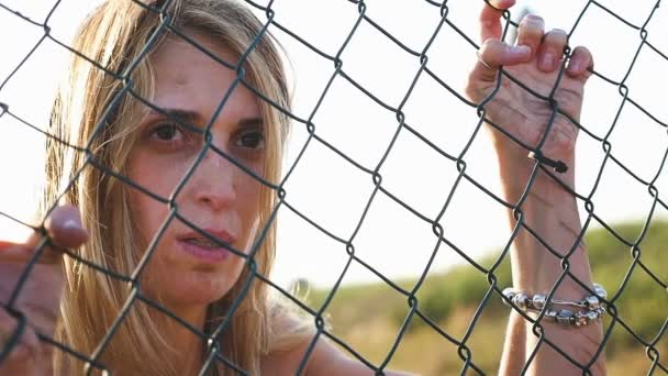sad crazy woman looks at something clinging to a net