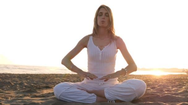 Jóga na pláži při západu slunce: sukhasana pozice