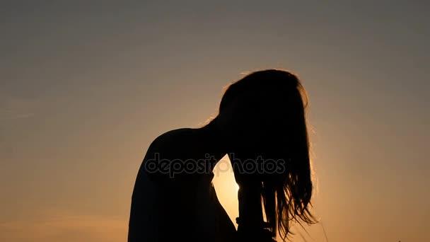 Sagoma di donna sexy al tramonto mentre che pettina i capelli con le mani