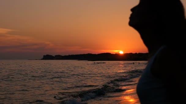 Siluetta della donna al tramonto scuotendo i suoi lunghi capelli - rallentatore