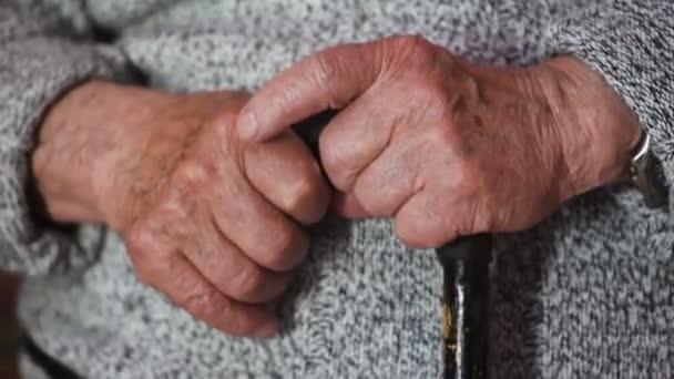 Starý muž vrásčité ruce držící hůl
