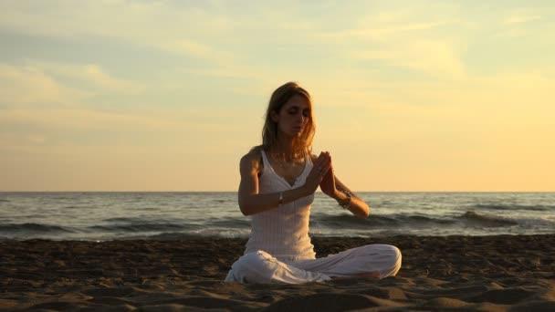 Žena, která dělá jógu: medituje na pláži při západu slunce