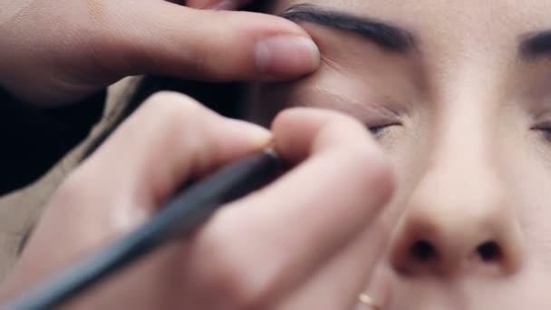 Applying  eye shadow On beautiful womans Eyes