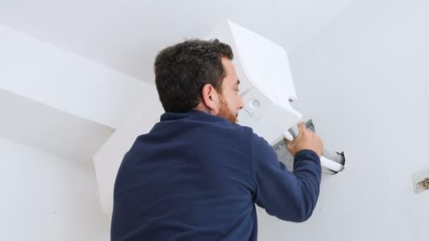 Techniker installiert die Klimaanlage an der Wand