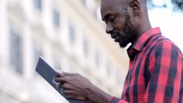 mladých balck člověka pomocí digitálních tabletu na ulici