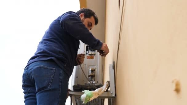 Techniker repariert Klimaanlage an der Wand