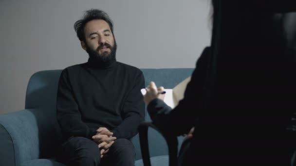 mladý muž mluví s psychologem, sedí psychoterapeut