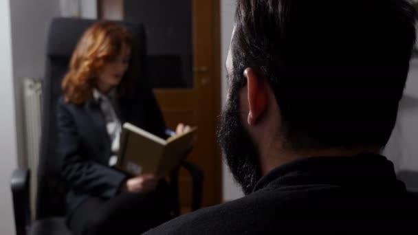 psycholog poslouchá svého pacienta, psaním poznámek