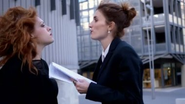 two young business women argue violently in the street