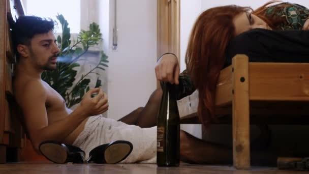 Drogen- und Alkotrinksüchtiges Paar im Zimmer, raucht einen Joint