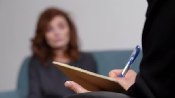 Terapeutické sezení: psycologist dělají poznámky poslouchat svého pacienta