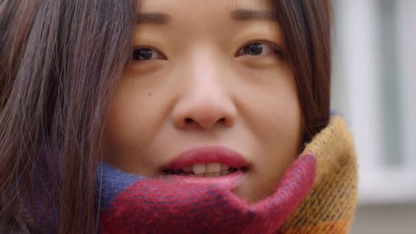 close up portrait of pretty asian woman smiling at camera outdoor
