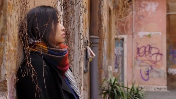 Depressed and sad chinese woman alone, leaning against a wall