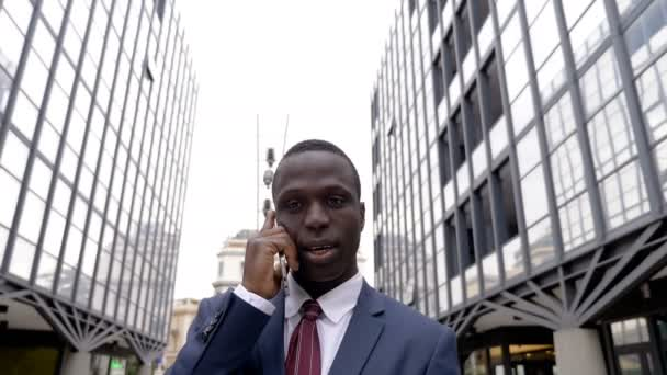 Handsome busy black american manager talking by phone in the city