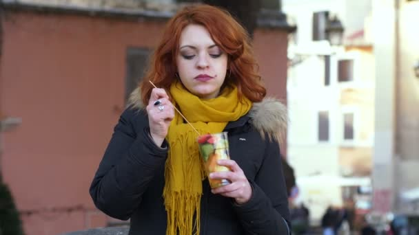 pretty young cute woman in the street eating fruit salad
