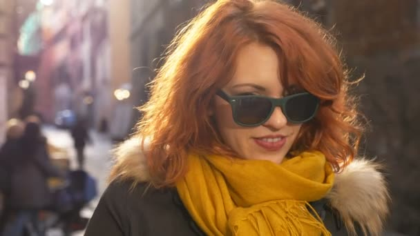 sensual woman with red hair plays with sunglasses flirting with the camera