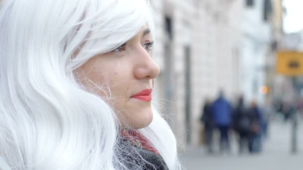Pensive funny woman with white wig in the street