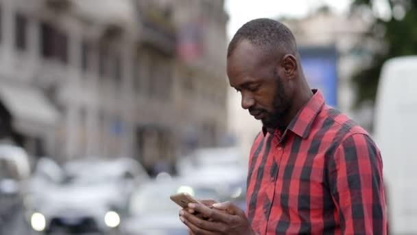 schöner schwarzer Mann mit Telefon in der Stadt