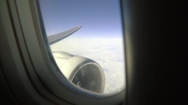 schiefe Flugzeugfenster Blick auf Flugzeugturbine über Wolken.