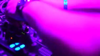 Hands of DJ tweak various track controls on djs deck