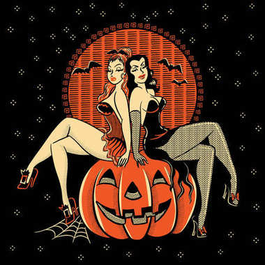 Halloween ghoulish glamour twins sitting on a carved pumpkin head.