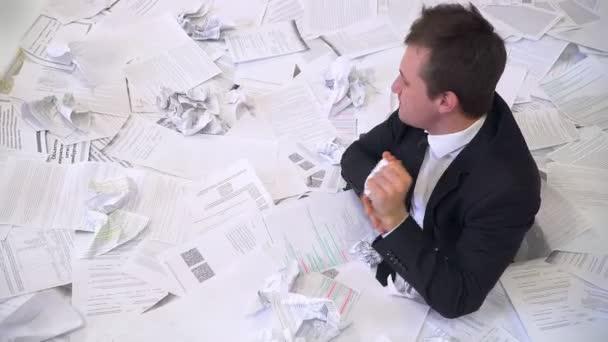 muž v kanceláři topí v papíru