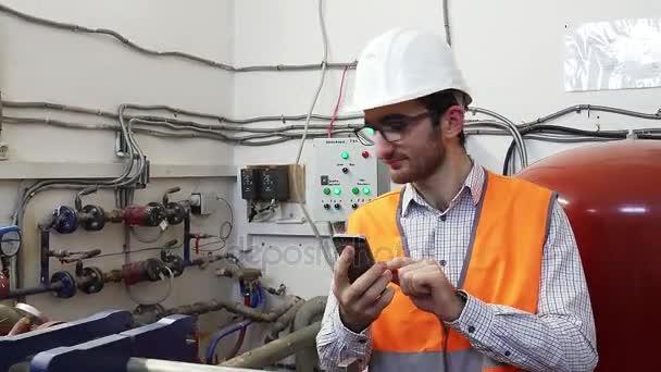 Ingenieur Heizungsbauer arbeitet vor Ort und telefoniert
